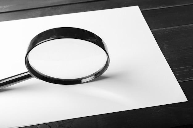 Vergrootglas en blanco papier op houten tafel Premium Foto