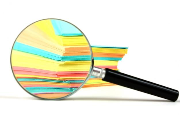 Vergrootglas en een stapel papier voor notities Premium Foto
