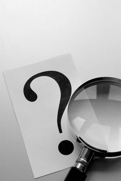 Vergrootglas en een vraagteken op het papier Premium Foto