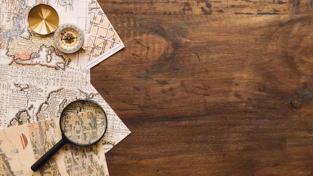 Vergrootglas en kompas op kaarten Gratis Foto