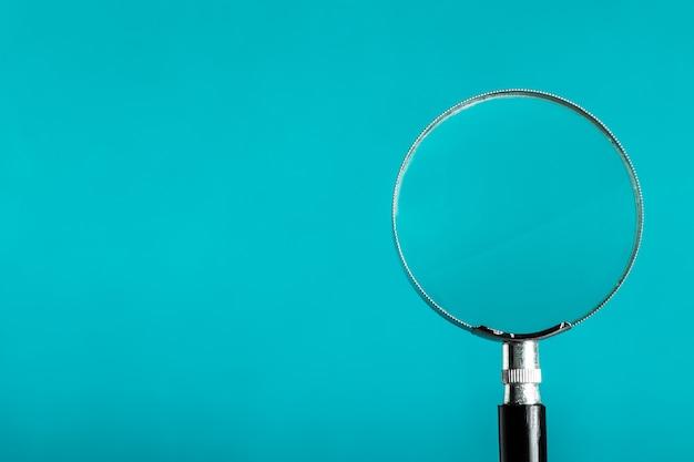 Vergrootglas op blauwe kleurenachtergrond. Premium Foto
