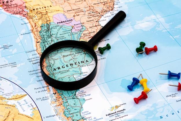 Vergrootglas op de wereldkaart selectieve nadruk in argentinië. - economisch en bedrijfsconcept. Premium Foto
