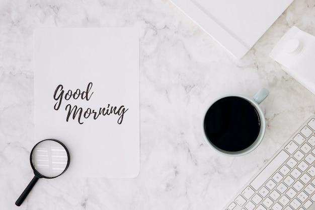 Vergrootglas op goedemorgen papier met koffiekopje; dagboek en toetsenbord op wit marmeren bureau Gratis Foto