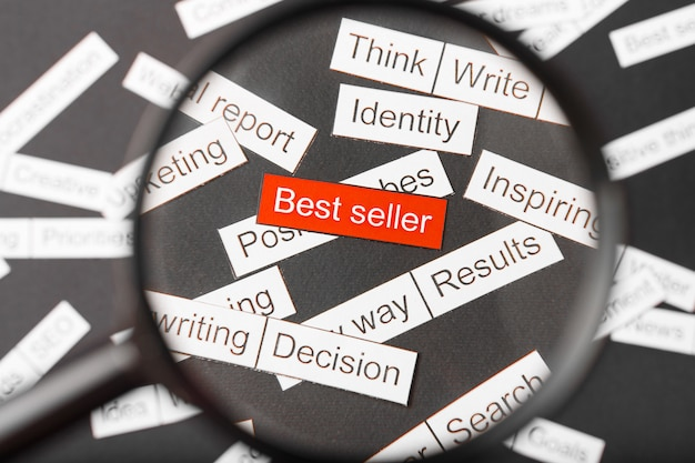 Vergrootglas over de rode inscriptie bestseller uit papier gesneden. omringd door andere inscripties. word cloud concept. Premium Foto