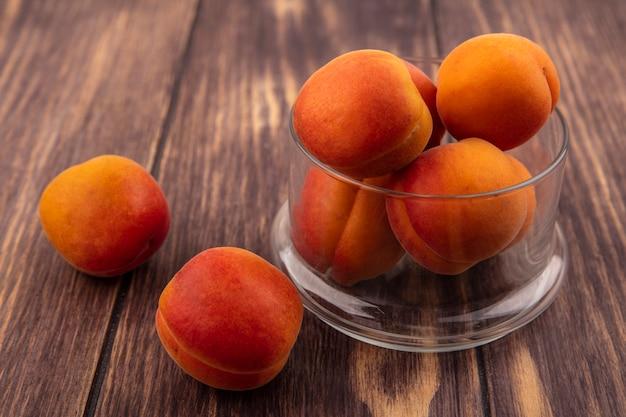 Vergrote weergave van abrikozen in glazen pot en op houten achtergrond Gratis Foto