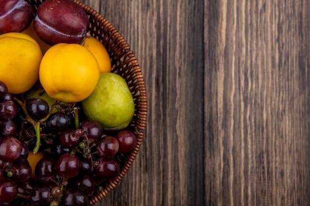 Vergrote weergave van fruit als druivenplukken nectacots in mand op houten achtergrond met kopie ruimte Gratis Foto