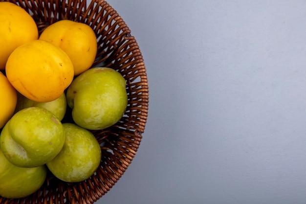 Vergrote weergave van fruit als groene plukken en nectacots in mand op grijze achtergrond met kopie ruimte Gratis Foto