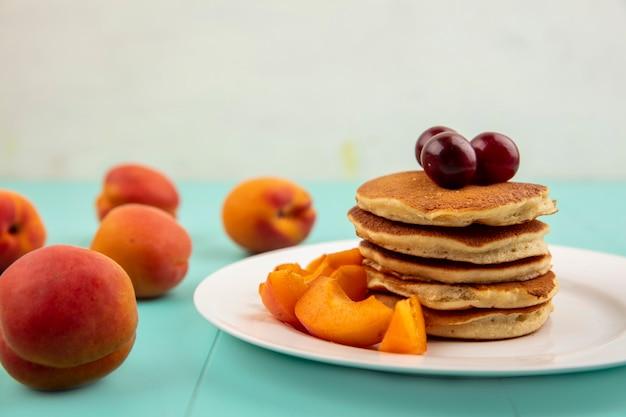 Vergrote weergave van pannenkoeken met abrikozenplakken en kersen in plaat en abrikozen op blauwe ondergrond en witte achtergrond Gratis Foto