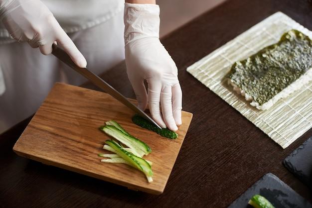Vergrote weergave van proces ter voorbereiding van heerlijke rollende sushi in restaurant. vrouwelijke handen in wegwerphandschoenen komkommer snijden op een houten bord. Premium Foto