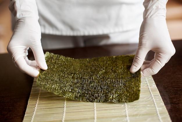 Vergrote weergave van proces ter voorbereiding van rollende sushi. de handen van de chef houden een vel nori vast en beginnen te koken Premium Foto