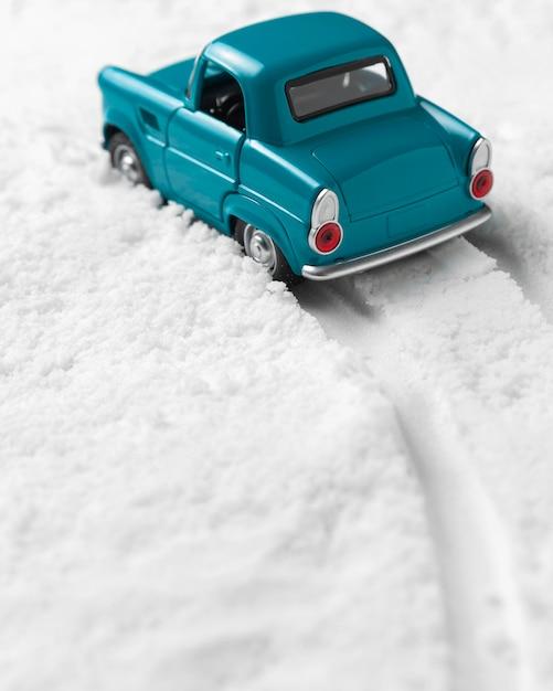 Vergrote weergave van speelgoedauto in de sneeuw Premium Foto