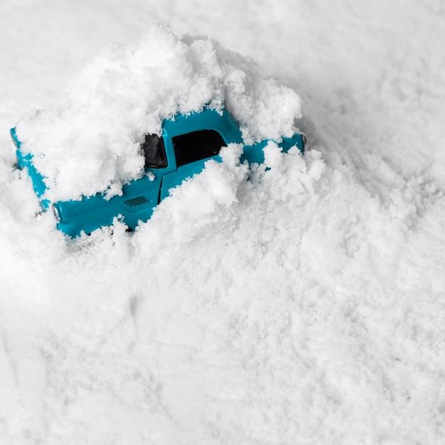 Vergrote weergave van speelgoedauto in de sneeuw Gratis Foto