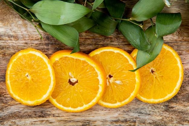 Vergrote weergave van stukjes sinaasappel op houten achtergrond versierd met bladeren Gratis Foto