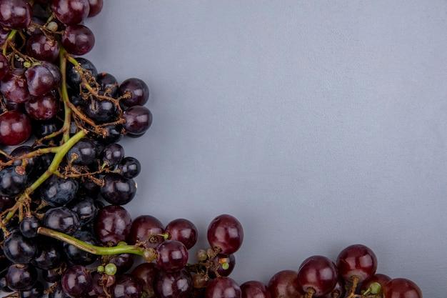 Vergrote weergave van zwarte en rode druiven op grijze achtergrond Gratis Foto