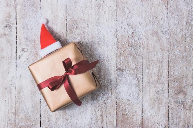 Verguld cadeau met een rode strik en een kerstmuts Gratis Foto