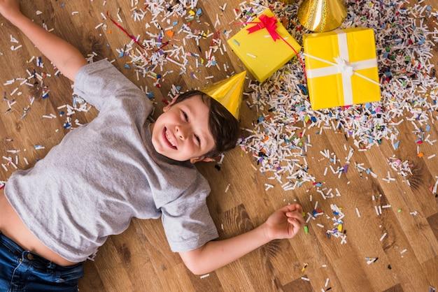 Verhoogde mening van een gelukkige jongen die op hardhoutvloer ligt met confettien; geschenkdozen en feestmuts Gratis Foto