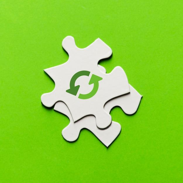 Verhoogde mening van recyclingspictogram op wit raadselstuk over groene achtergrond Gratis Foto