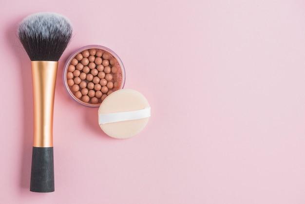 Verhoogde weergave van bronzing parels; spons en make-upborstel op roze achtergrond Gratis Foto