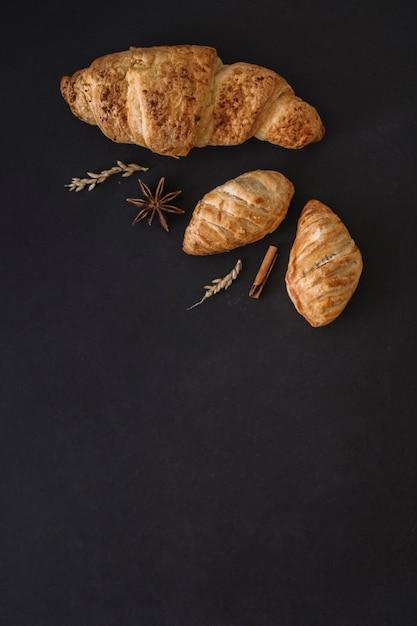 Verhoogde weergave van croissants; specerijen en granen op zwarte achtergrond Gratis Foto