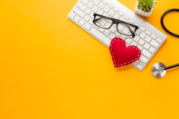 Verhoogde weergave van draadloos toetsenbord; bril; vetplant; met gestikt doek speelgoed over gele achtergrond Gratis Foto