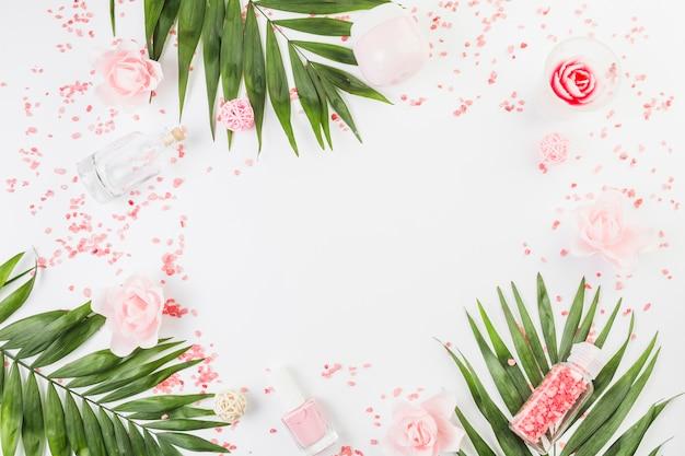 Verhoogde weergave van himalayazout; verlaat; nagellak; fles; vochtinbrengende crème en bloemen op witte achtergrond Gratis Foto