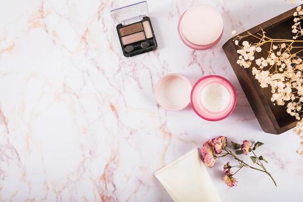 Verhoogde weergave van oogschaduwpoeder en vochtinbrengende crème Gratis Foto