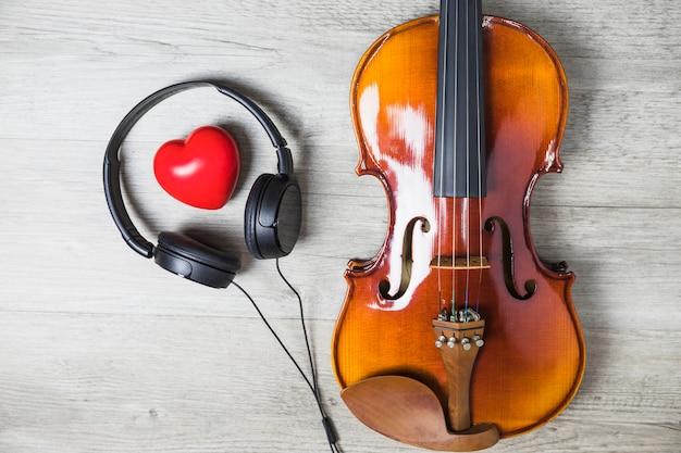 Verhoogde weergave van rood hart omgeven met hoofdtelefoon en houten klassieke gitaar op grijze tafel Gratis Foto
