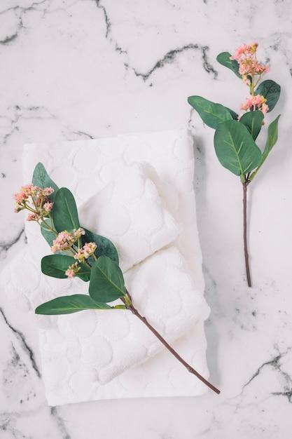 Verhoogde weergave van roze bloemen en witte servetten op marmeren oppervlak Gratis Foto
