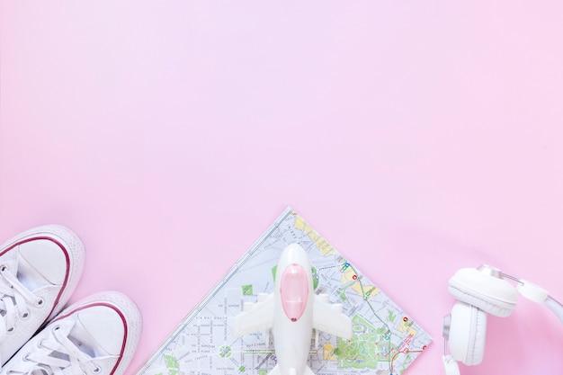 Verhoogde weergave van schoenen; kaart; vliegtuig en oortelefoon op roze achtergrond Gratis Foto