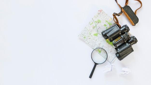 Verhoogde weergave van verkreukeld tissuepapier; kaart; verrekijker en vergrootglas op witte achtergrond Gratis Foto
