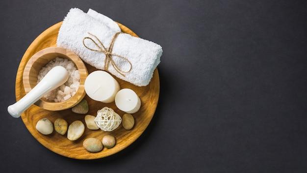Verhoogde weergave van zout; handdoek; kaarsen en spa stenen op houten plaat over zwarte achtergrond Gratis Foto