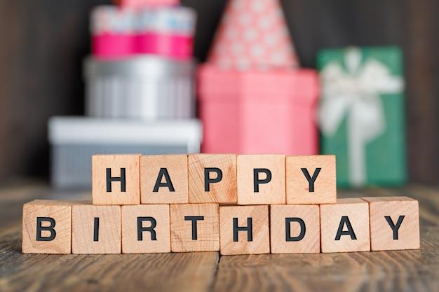 Verjaardag concept met geschenkdozen, houten kubussen op houten tafel zijaanzicht. Gratis Foto