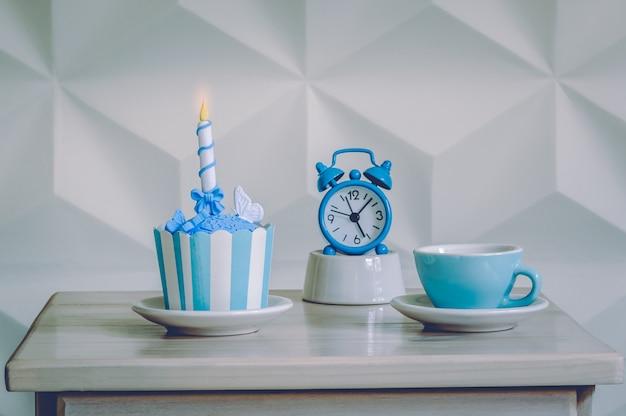 Verjaardag cupcake dessert met blauwe wekker en kop thee Premium Foto