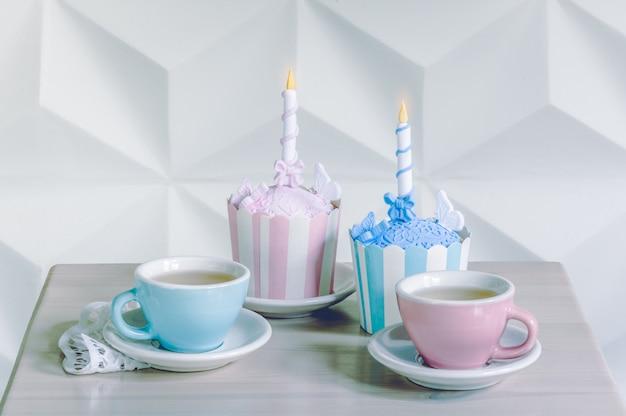 Verjaardag cupcakes met verjaardagskaars en kop theeën Premium Foto
