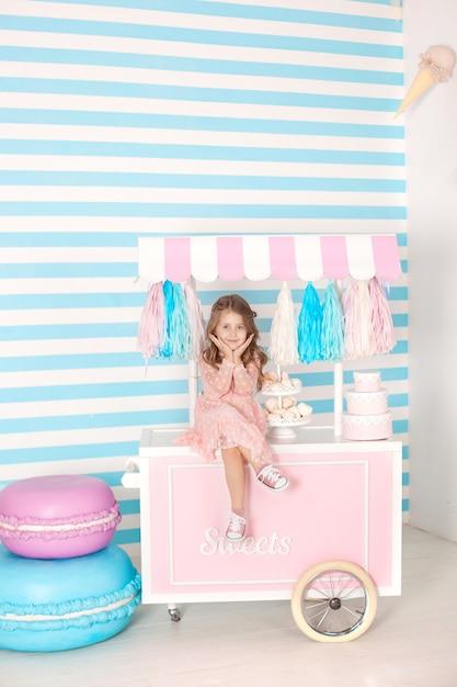 Verjaardag en gelukconcept - gelukkige meisjezitting op een karretje met roomijs en snoepjes Premium Foto