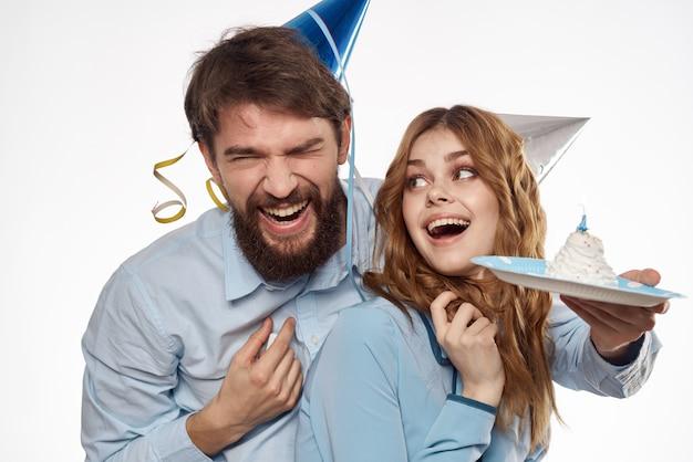 Verjaardag man en vrouw met een cupcake en een kaars in een feestmuts, wit Premium Foto