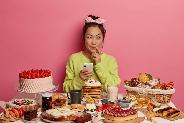 Verjaardag vrouw denkt uit te nodigen op feestje stuurt berichten naar vriend via mobiele telefoon bakt verschillende desserts voor gasten verheugt zich op het eten van lekker zoet eten Gratis Foto