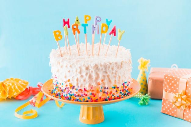 Verjaardagscake met cadeau en accessoires op blauwe achtergrond Gratis Foto