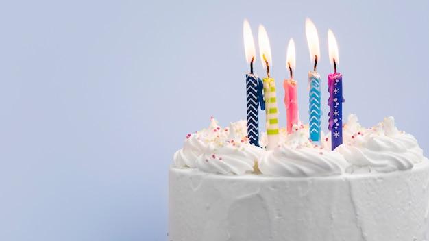 Verjaardagscake met kaarsen op blauwe achtergrond Gratis Foto