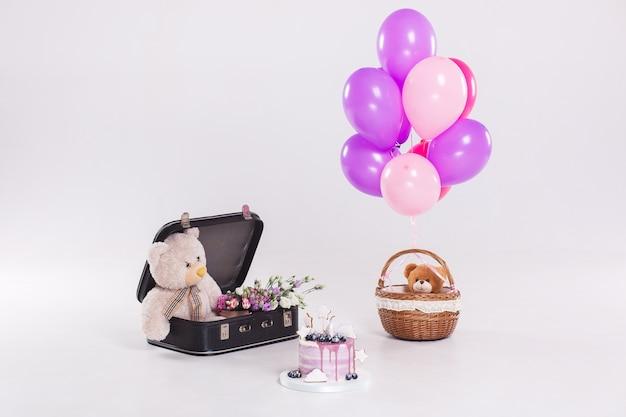 Verjaardagscake, teddybeer in uitstekende die suitecase en ballons op witte achtergrond wordt geïsoleerd Gratis Foto