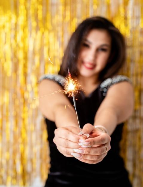Verjaardagsfeest. mooie jonge vrouw met sterretje en ballon op gouden achtergrond Premium Foto