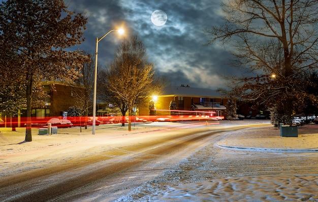 Verkeer bij nacht in de behandelde sneeuw, de mooie stad van de nachtweg Premium Foto