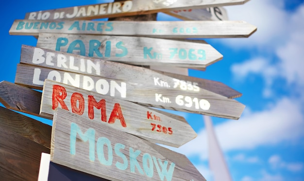 Verkeers verkeersbord inclusief moskou, roma, londen, berlijn, parijs, rio de janeiro op blauwe hemelachtergrond in retro stijl Gratis Foto