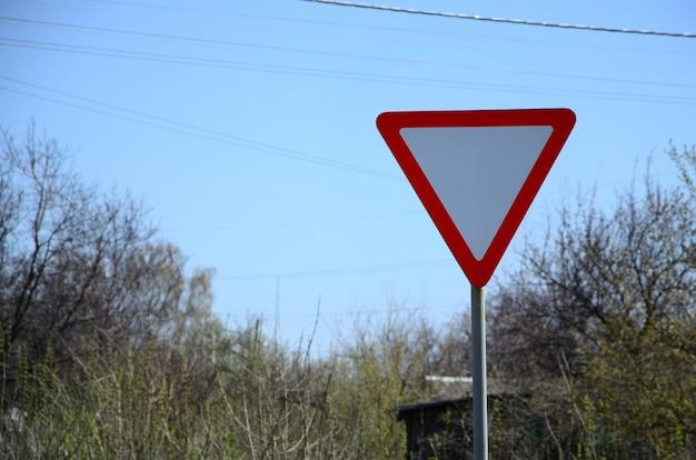 Verkeersbord in de vorm van een witte driehoek. weggeven Premium Foto