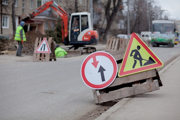 Verkeersborden, omleiding, wegreparatie op straat, graafgat voor vrachtwagens en graafmachines. Premium Foto