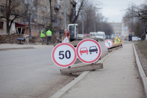 Verkeersborden, omweg, weg reparatie op straat achtergrond, vrachtwagen en graafmachine graafgat Premium Foto