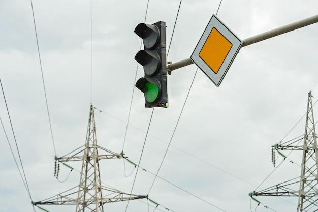 Verkeerslicht met het bord van de hoofdweg tegen Premium Foto