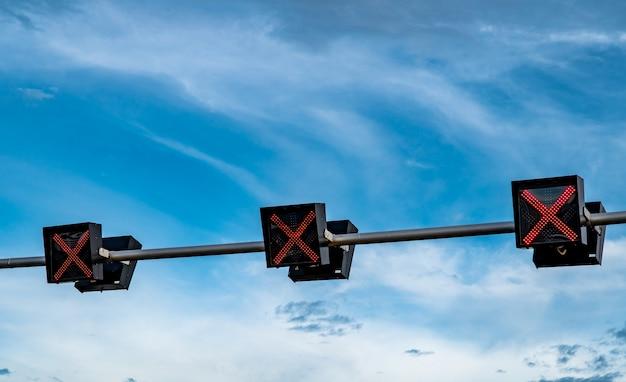 Verkeerslichtlicht met rode kleur van dwarsteken op blauwe hemel en witte wolkenachtergrond. Premium Foto