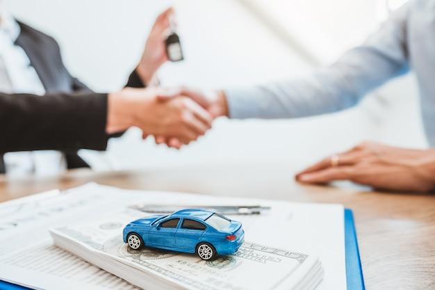 Verkoop agent handdruk deal overeenkomst succesvolle auto lening contract met klant en teken overeenkomst contract verzekering auto. Premium Foto