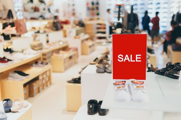 Verkoop etiketstandaardsjabloon op planken in kledingwinkel of winkelfront voor verkooppromotie en kortingsinformatie. Premium Foto